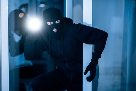Time For Crime. Cautious burglar looking and peeping into building through window or glass door with torch