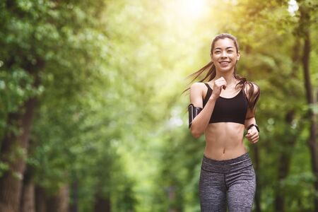 Healthy Lifestyle. Sporty Asian Girl In Jogging In City Park, Enjoying Morning Workouts, Preparing For Marathon