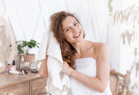 Positive pretty girl drying her beautiful hair with towel after shower, home interior, free space