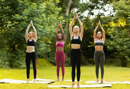 Group of diverse girls practicing yoga at park on sunny day