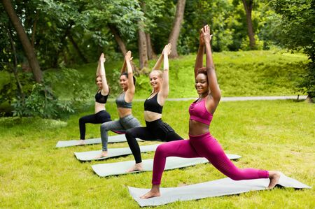 Diverse young women making warrior pose during their outdoor yoga practice at park, copy space