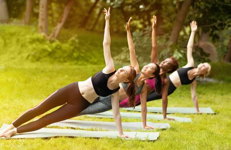 Diverse young women practicing yoga together at park on sunny summer day