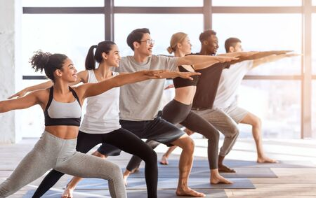 Multiethnic group of sporty people practicing yoga, standing in Warrior two pose in modern loft studio, side view