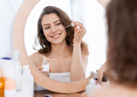 Cheerful girl standing in front of mirror at home, using serum for hydrating skin at summer