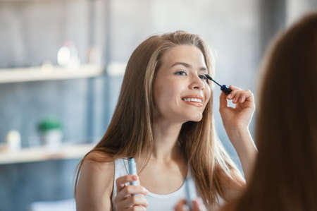 Beauty and makeup. Sweet lady applying mascara on her eyelashes near mirror at bathroom