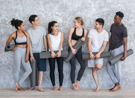 Healthy Lifestyle Concept. Group of sporty people with yoga mats resting after class near grey wall in fitness studio