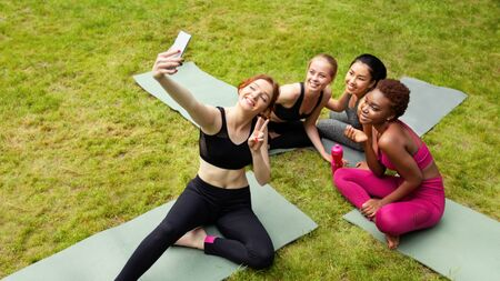 Happy diverse girls taking selfie after yoga class outdoors, copy space. Panorama