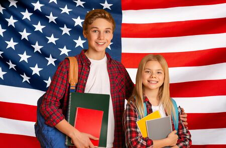 Education In United States. Happy little boy and girl school pupils with backpacks and notepads standing over American flag background, collage