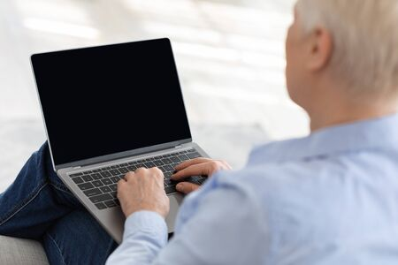 Elderly woman using laptop with blank screen at home, making video call with relatives or doctor, mockup image with copy space, over shoulder view