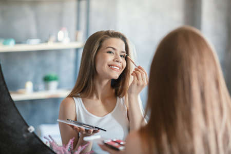 Home makeup routine. Charming lady applying eyeshadow on her face near mirror at bathroom