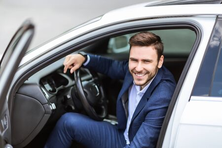 Portrait of smiling corporate employee sitting on drivers seat of his car