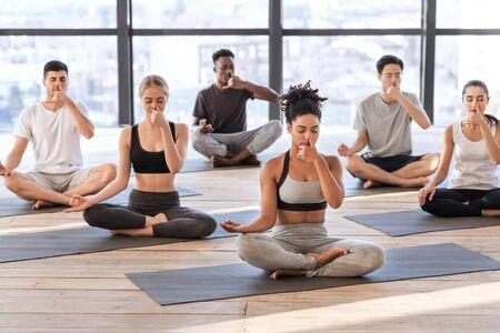 Young men and women in yoga studio practicing alternate nostril breathing exercises together, sitting on mats and doing nadi shodhana pranayama asana Stock Photo