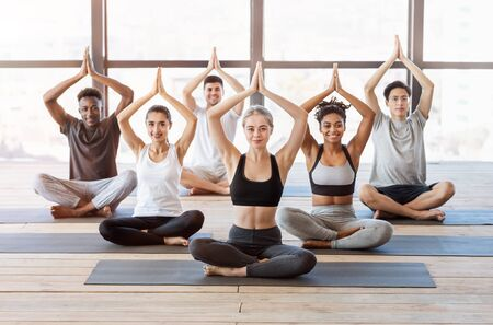 International Yoga Class. Group Of Multiethnic Sporty People Sitting In Tree Pose On Mats In Modern Loft Studio, Free Space