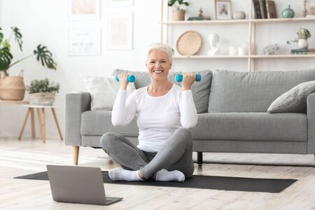 Home Training. Smiling Senior Woman Excercising With Dumbbells In Front Of Laptop, Watching Online Tutorials, Enjoying Healthy Lifestyle, Free Space Foto de archivo