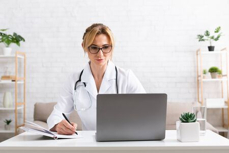 Work from home. Woman doctor at desk in room with laptop, in interior, copy space