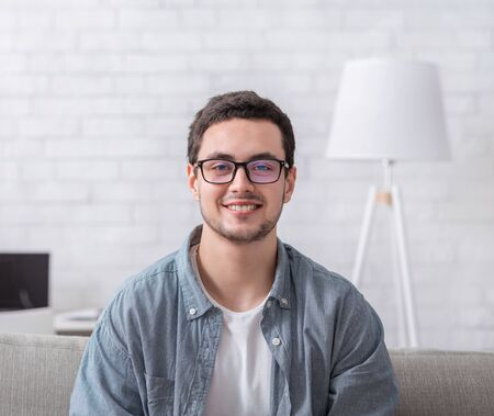 Modern lifestyle. Smiling guy with glasses sits on couch in bright interior of living room and keeps blog, free space, close up