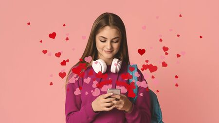 Smiling teenage girl with headphones is typing on smartphone, hearts fly out of smartphone on pink background, studio shot Stock fotó