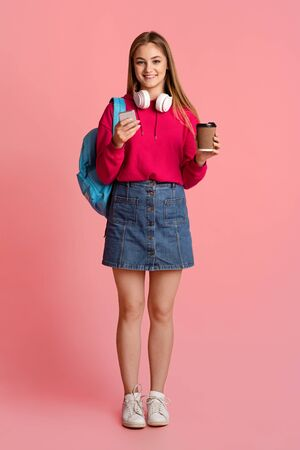 Modern smiling teenage girl with cup of coffee takeaway, backpack and with headphones, checking for smartphone, free space
