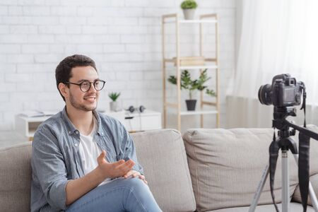 Presentation and review. Young man in glasses tells something to camera in interior of living room Stock fotó