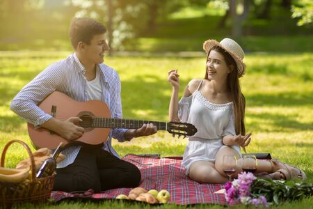 Romantic boyfriend playing guitar and singing song for his girlfriend during summer picnic at park Archivio Fotografico