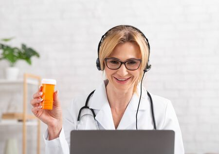 Doctor recommends a medicine. Woman in headphones in white coat holds jar in hand, laptop near, in interior Stock fotó
