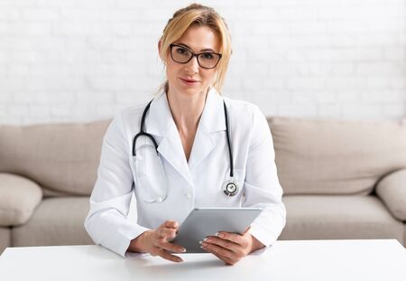 Doctor and online medical support. Attractive adult female doctor in white coat with tablet in hands in interior