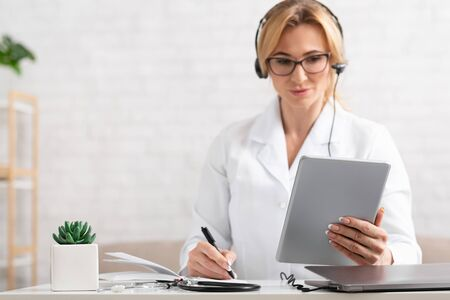 List of symptoms of patient. Woman doctor with headphones holding tablet in hands and looking at it, makes notes in notebook, at workplace Stock fotó