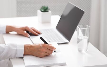 Write recipe online. Female hands make entry in notebook on table with laptop with blank screen Stock fotó