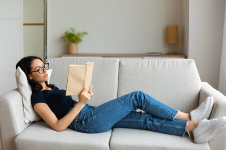 Student Girl Reading Book Studying Lying On Couch At Home. Weekend Relaxation Concept