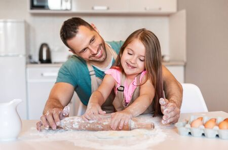 Happy Dad And Daughter Rolling Out Dough Baking Cake Together In Kitchen Indoors. Selective Focus