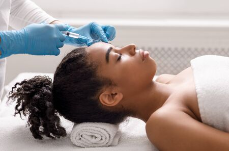 Anti-aging injections for attractive african american woman at spa salon 免版税图像