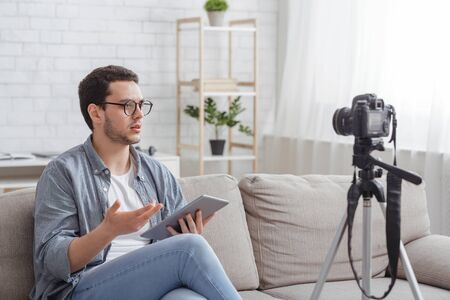 Blogger opinion. Serious guy with glasses, with tablet in hands sits on couch, makes video on camera in living room interior