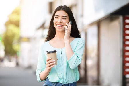 Modern Communication. Cheerful asian girl walking outdoors with takeout coffee and talking on cellphone, enjoying summer day in city