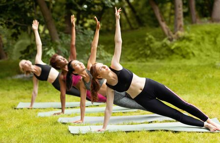 Beautiful multiracial girls doing side plank yoga pose during group practice at park