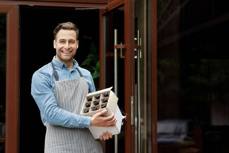 Beer business. Smiling barman in apron holds cardboard box with bottles at front door, free space
