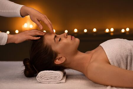 Tranquil girl getting head massage in romantic atmosphere at spa salon, side view