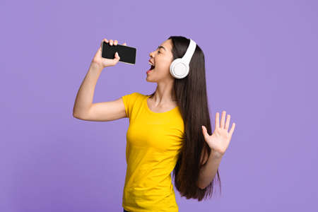 Candid asian girl singing into smartphone like microphone while listening music via wireless headphones over purple background, copy space