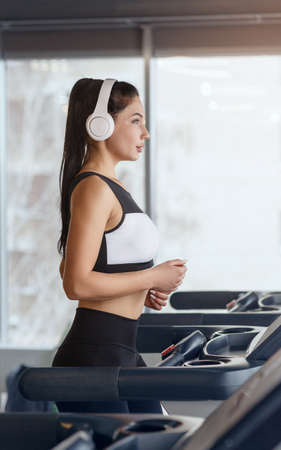 Sportive girl in headset enjoying favorite music while running on treadmill at health club