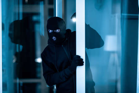 Burglary Concept. Watchful thief lurking into residential building through open front door, entering enclosed property Zdjęcie Seryjne