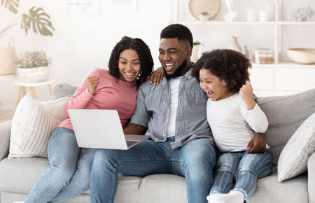 Online Lottery. Excited African American Family Of Three Celebrating Win With Laptop, Sitting On Couch In Modern Living Room