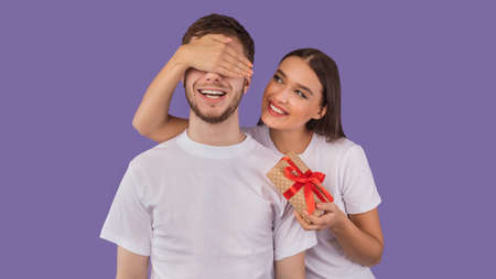 Girl covering her boyfriend eyes and giving him present isolated on pastel purple studio wall