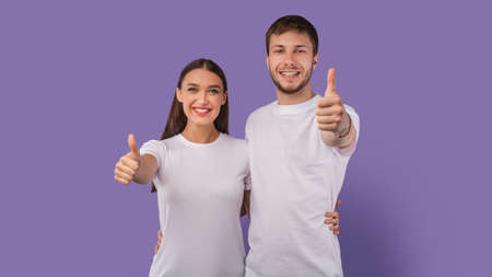 We Recommend. Excited guy and girl making thumbs up gesture, embracing on pastel purple studio wall, banner