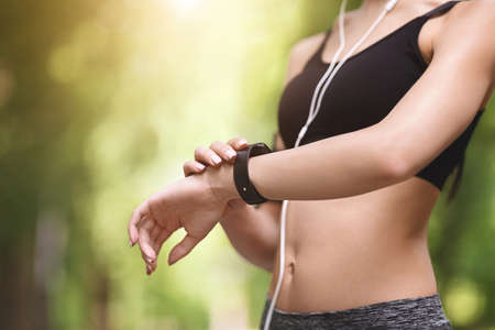 Unrecognizable athlete woman checking indicators at fitness bracelet, having break during jogging outdoors, looking at smartwatch, cropped image