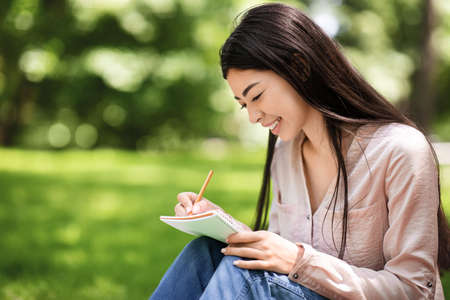 Young asian student girl writing notes to notebook while sitting on lawn in summer park, closeup shot with selective focus and copy space