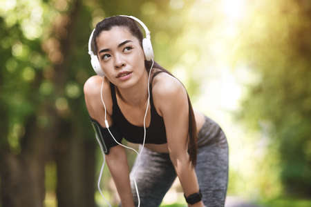 Sporty Lifestyle. Motivated Asian Girl Taking Rest During Jogging In City Park, Having Break, Wearing Armband And Headphones