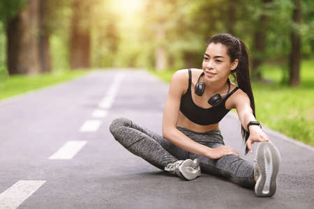 Young asian girl stretching legs before jogging outdoors, warming up for morning workout, sitting on path in park