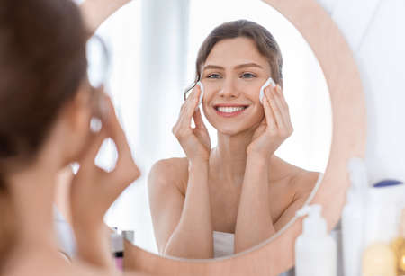 Skincare. Young cheerful woman looking at mirror and cleaning her face with cotton pads at home