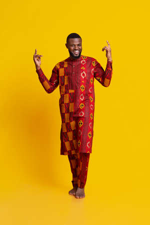 Cheerful black man in african costume gesturing over yellow background, pointing up