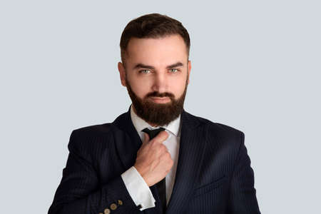 Handsome gentleman in business suit adjusting his tie against light grey background