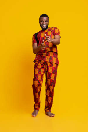Handsome cheerful black guy in authentic clothes flirting over yellow studio background Standard-Bild